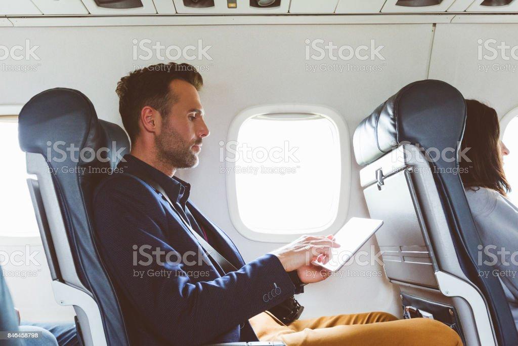 Geschäftsmann mit digital-Tablette im Flugzeug Lizenzfreies stock-foto
