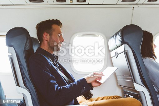 istock Businessman using digital tablet in airplane 846458798