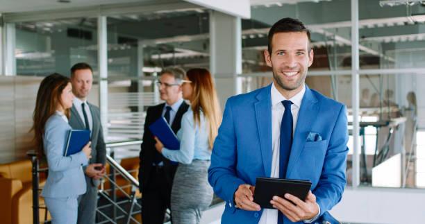 Businessman using digital tablet in office building hallway stock photo