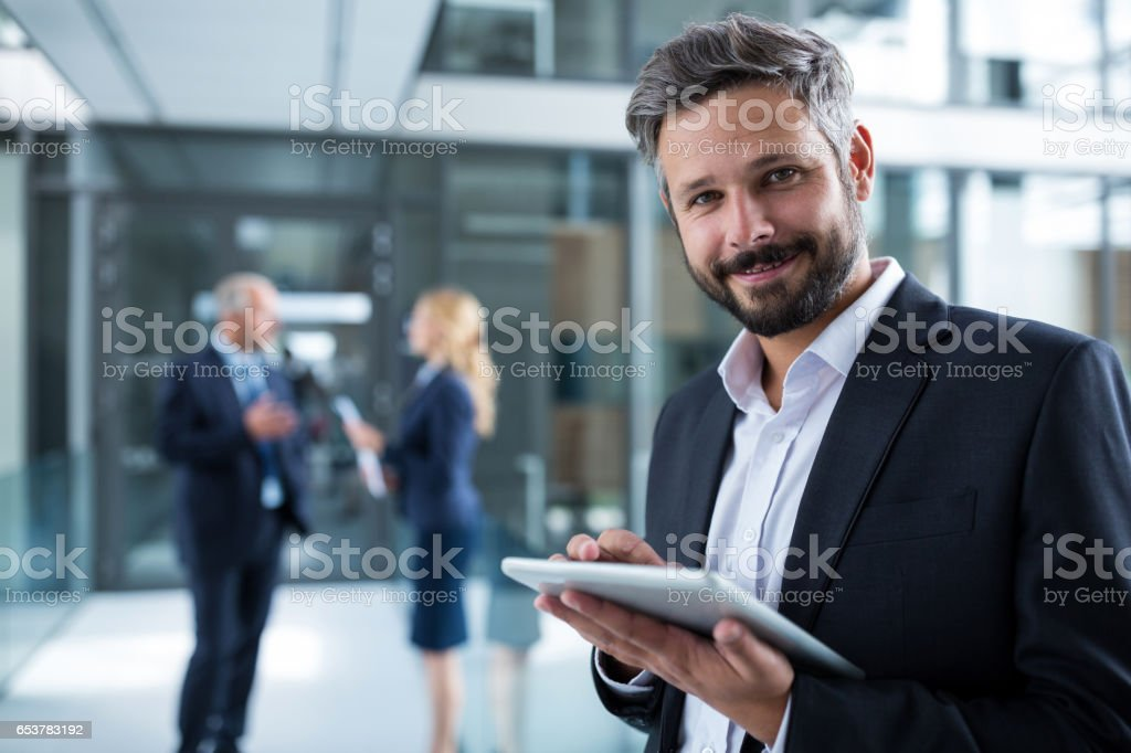 Businessman using digital tablet in office corridor Portrait of businessman using digital tablet in office corridor 30-34 Years Stock Photo