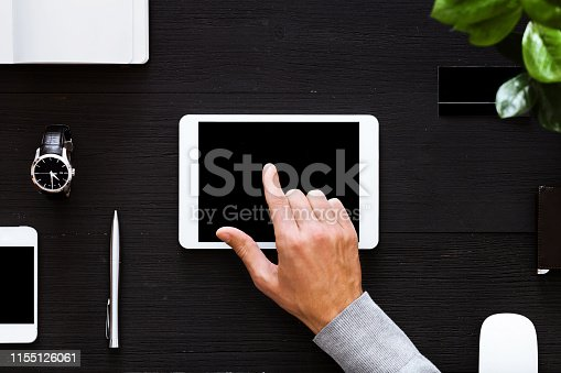 1134879628 istock photo Businessman using digital tablet mock up screen on business office table, male hand on computer device on work desk with gadgets, wooden black background modern workplace tabletop, top view above 1155126061