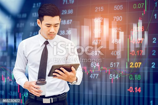 istock Businessman Using Digital Tablet on digital stock market financial exchange information and Trading graph background 865230922