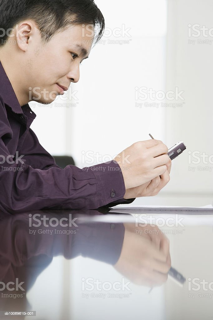 Businessman using electronic organiser, side view foto de stock libre de derechos