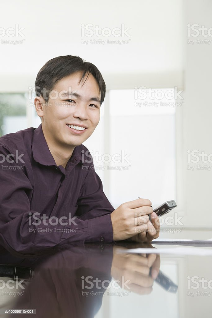Businessman using electronic organiser, smiling, portrait foto de stock royalty-free