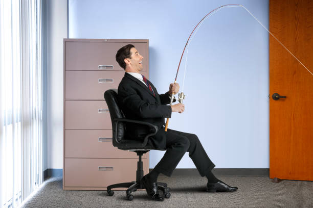 Businessman Using Fishing Pole In His Office - foto stock