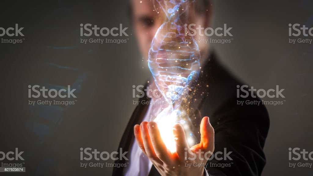 Businessman using his inner powers and holding glowing virtual DNA helix with energy sparks - business, creation, genetics, future and science concept stock photo