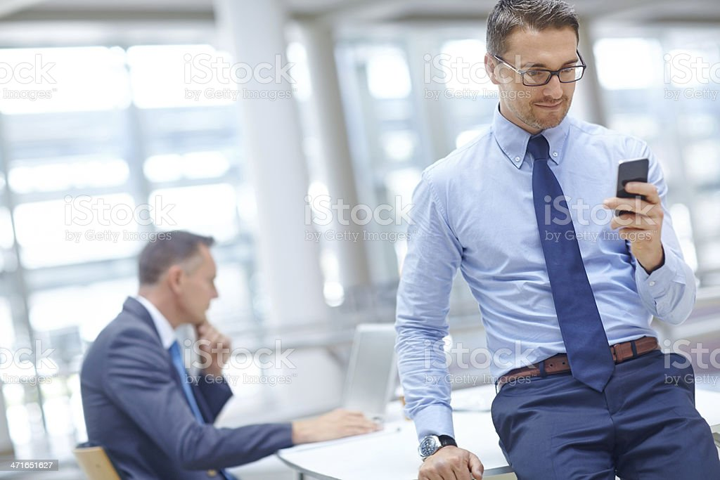 Businessman using his mobile phone in office royalty-free stock photo