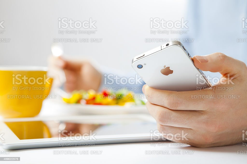 Businessman using iPhone and iPad royalty-free stock photo