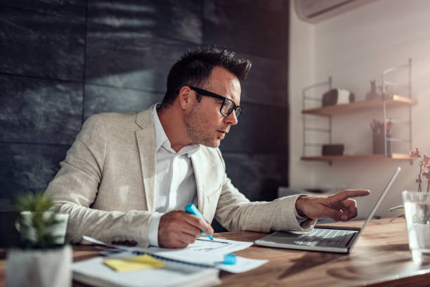 Businessman using laptop and highlighting text in his office Businessman wearing linen suit and eyeglasses sitting at his desk using laptop and highlighting text with blue marker in his office project manager stock pictures, royalty-free photos & images