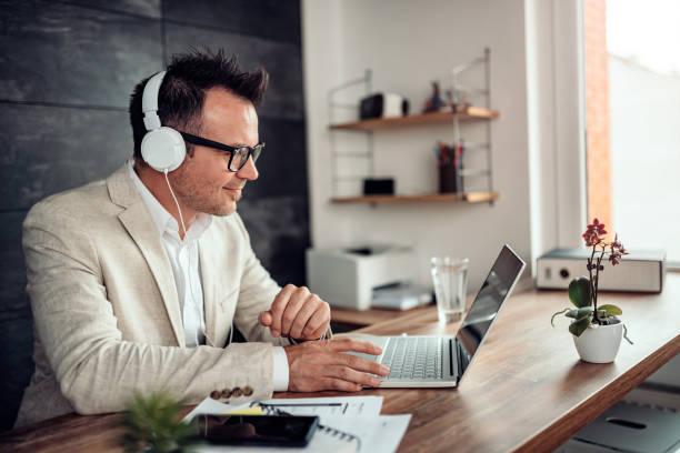 商人使用筆記本電腦和耳機上的聽音樂 - music 個照片及圖片檔
