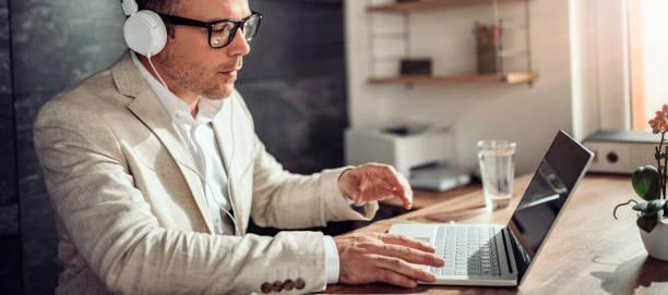 Hombre de negocios usando laptop y escuchando música en auriculares - foto de stock