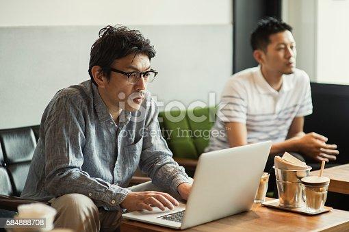 istock Businessman using laptop at cafe 584888708