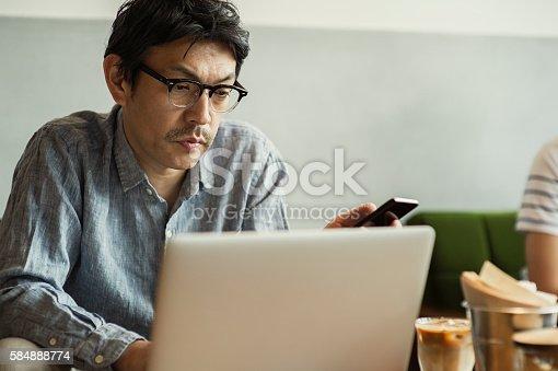istock Businessman using laptop at cafe 584888774