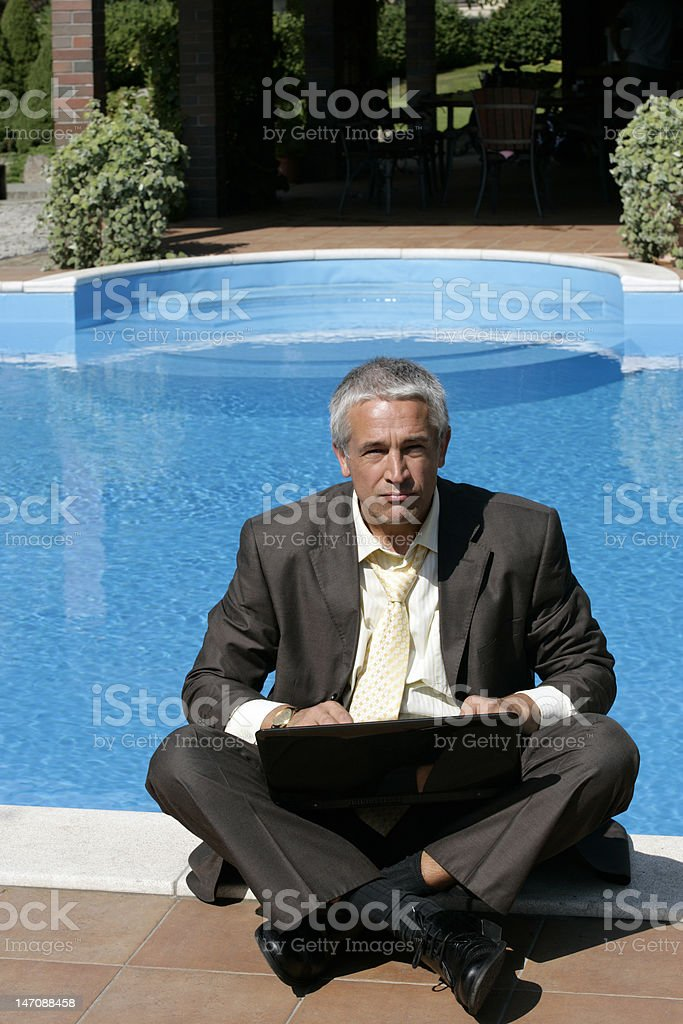 Businessman using laptop by the pool royalty-free stock photo