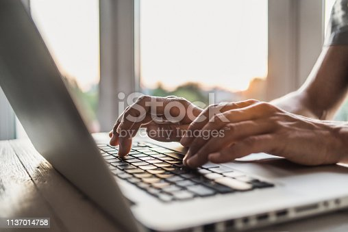 Men is typing on laptop computer keyboard