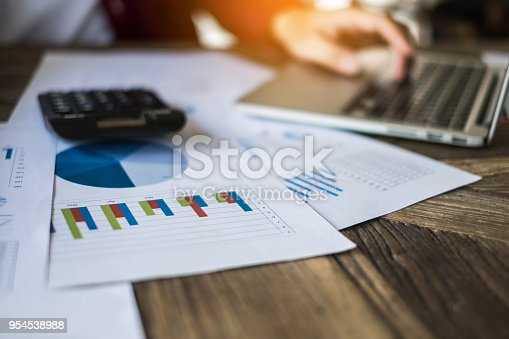 istock Businessman using laptop computer with financial paperwork on wooden desk. accounting concept. selective focus. 954538988