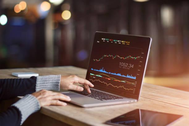 hombre de negocios con ordenador portátil para el análisis de mercado de valores de datos, gráfico de trading de forex, bolsa de comercio en línea, concepto de inversión financiera. en la pantalla del ordenador portátil son diseño para arriba. - inversión fotografías e imágenes de stock