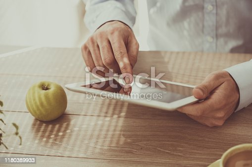 Close up of unrecognizable businessman using tablet.