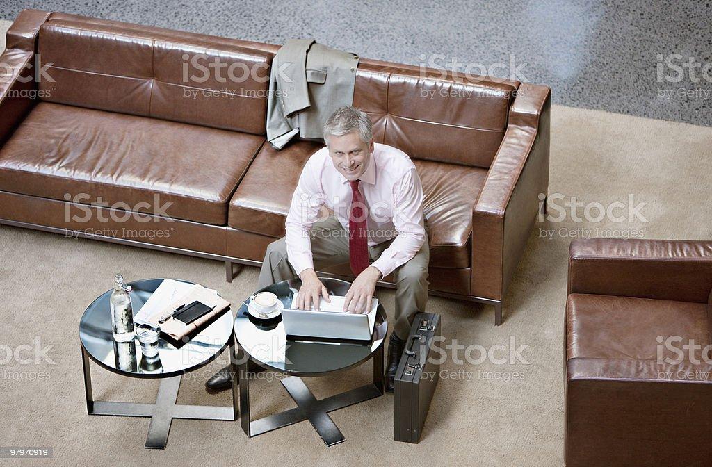 Businessman using laptop in lobby stock photo