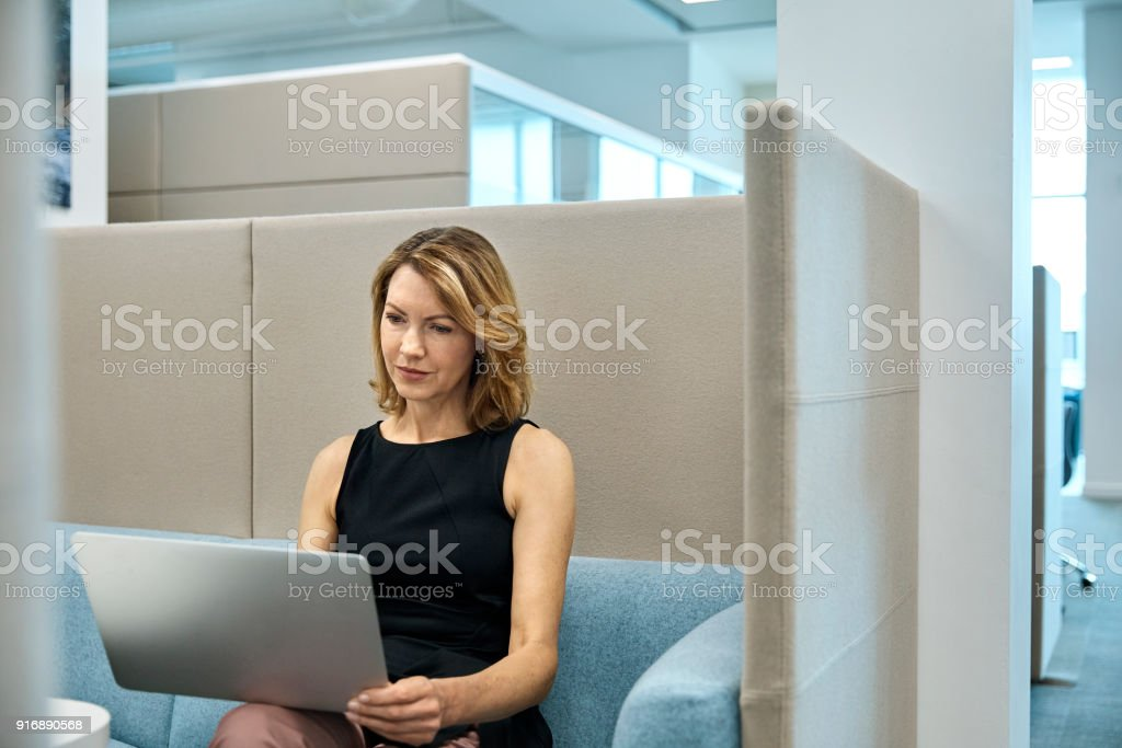 Mature businessman using laptop in office cubicle. Confident female...