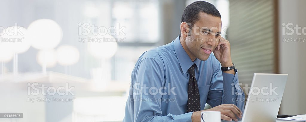 Businessman using laptop in office stock photo