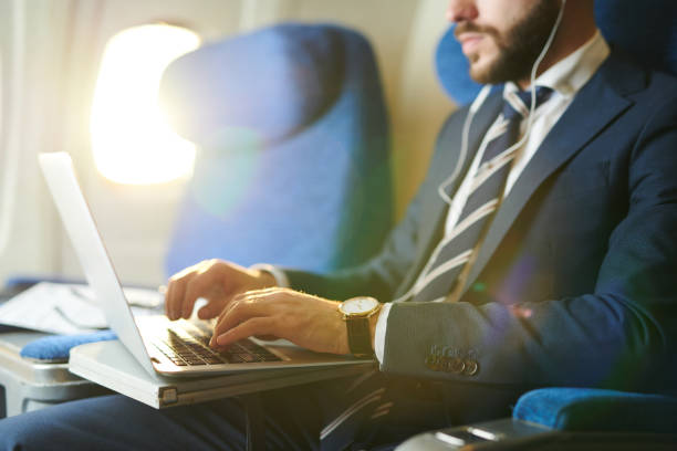 businessman using laptop in plane closeup - business travel stock pictures, royalty-free photos & images