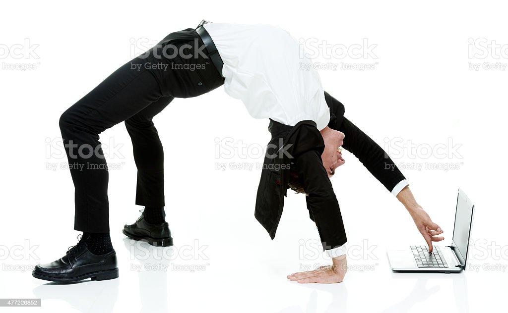 Businessman using laptop in yoga posture stock photo