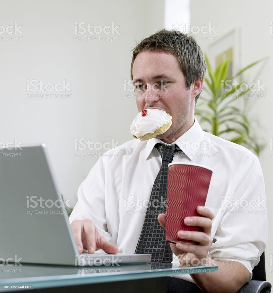 Businessman using laptop on desk, holding bun in mouth foto de stock royalty-free