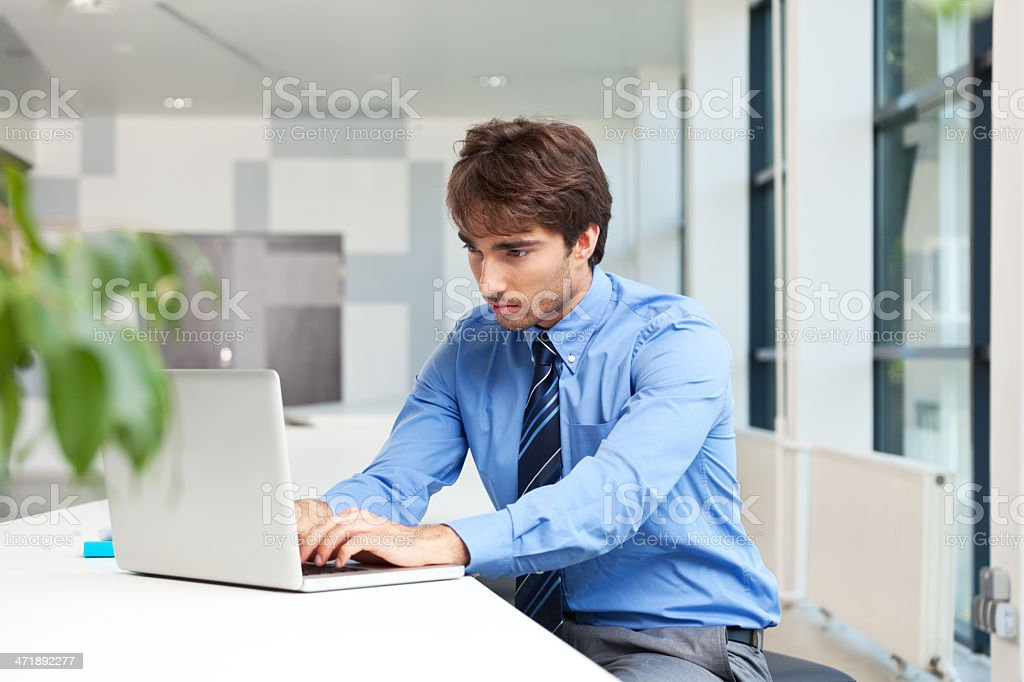 Businessman using laptop Businessman sitting in an office and working on the laptop.  Adult Stock Photo