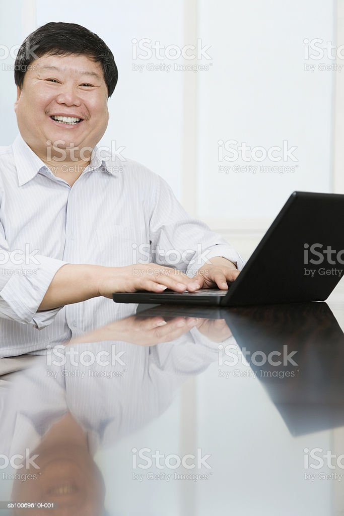 Businessman using laptop, smiling, portrait foto de stock libre de derechos