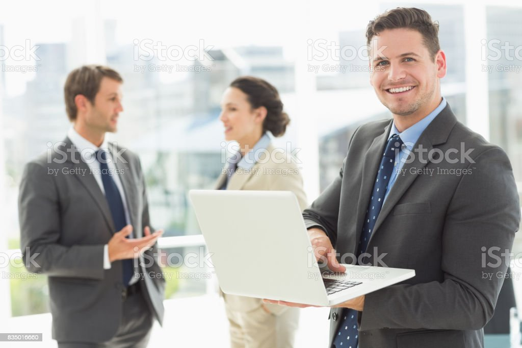 Businessman using laptop with colleagues discussing in office stock photo