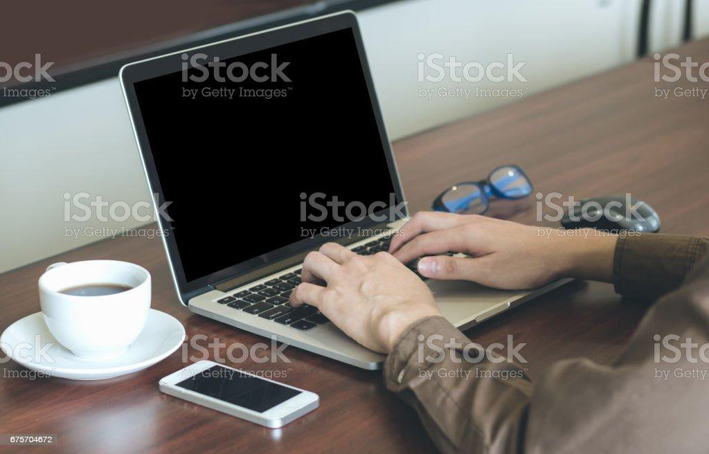 使用筆記本電腦在手機與辦公室工作的商人。 免版稅 stock photo