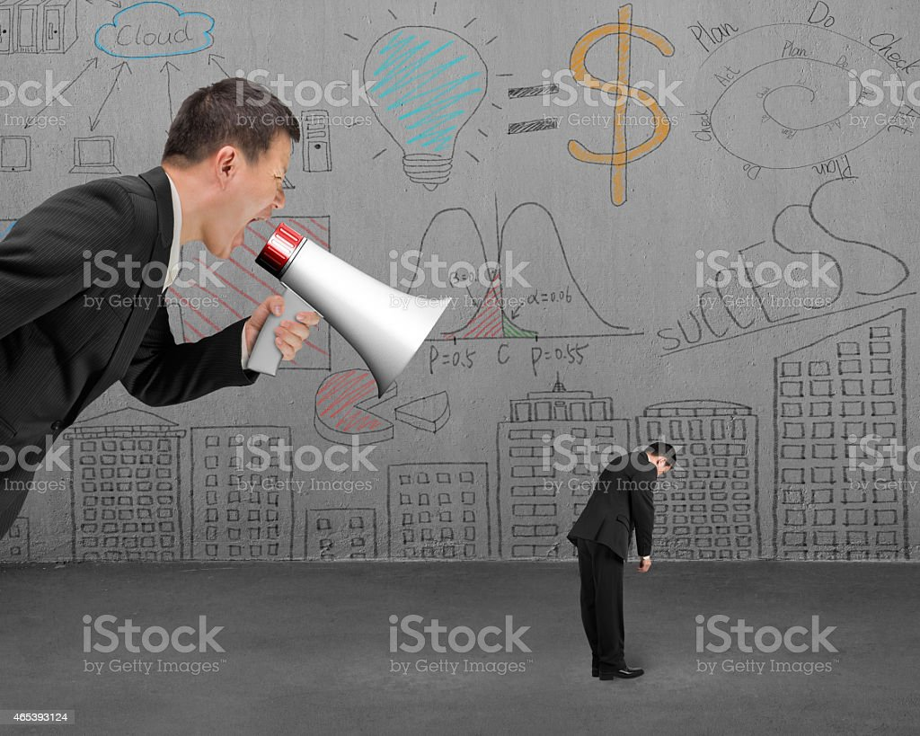 Businessman using megaphone yelling at his employee with doodles stock photo