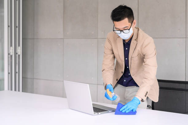 Businessman using microfiber cloth and alcohol sanitizer spray to clean laptop and table stock photo