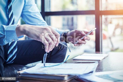istock Businessman using mobile checking e-mail while working in office. Modern technology and business concept. 914466002