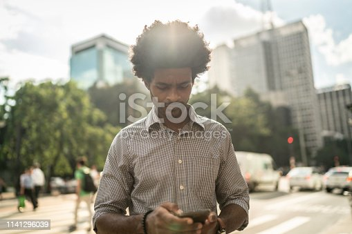 Businessman using mobile on the city