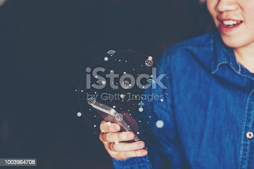 831899586istockphoto Businessman using mobile online icon social networking connection on screen 1003964708