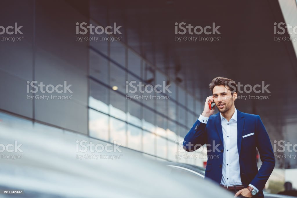 Businessman using mobile phone at airport parking lot stock photo