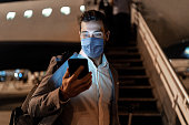 Businessman using mobile phone at airport using protective mask