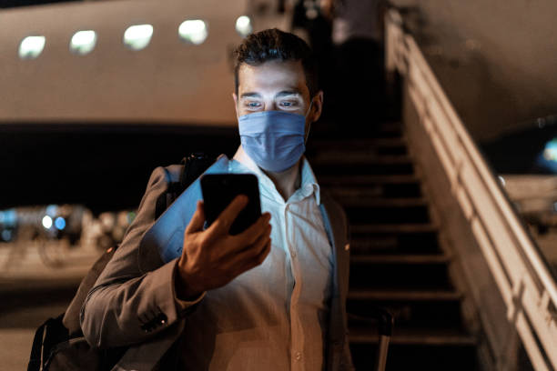 businessman using mobile phone at airport using protective mask - covid flight imagens e fotografias de stock
