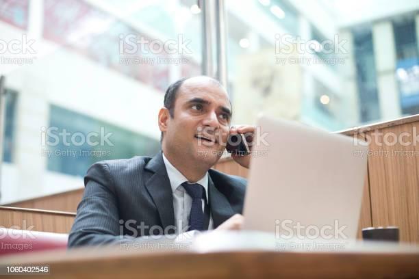 Businessman using mobile phone at cafe picture id1060402546?b=1&k=6&m=1060402546&s=612x612&h=cadmcjbenjsrco7eadoasip6mlep6wwbufuvz9lxc3m=