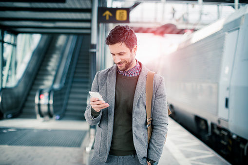 istock Businessman using mobile phone at train station 512432890