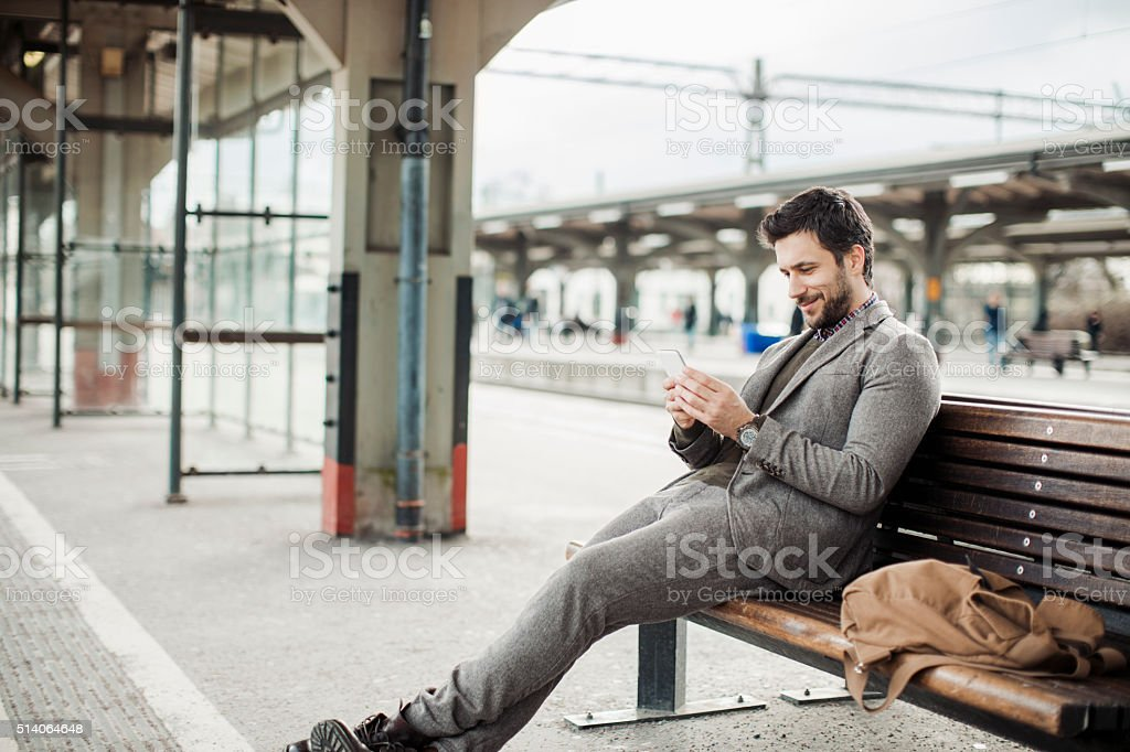 Businessman using mobile phone at train station stock photo
