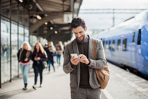 istock Businessman using mobile phone at train station 515473470