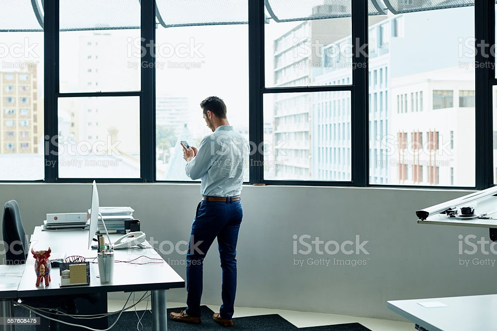 Businessman using mobile phone by office window stock photo