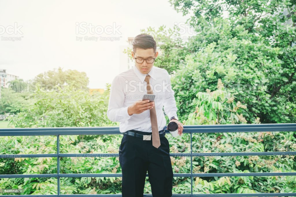 Businessman Using Mobile Phone Hand holding Coffee cup outdoor stock photo