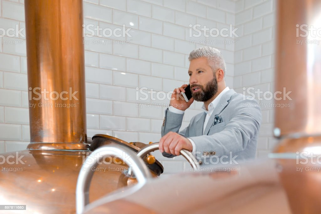 Businessman using mobile phone in his micro brewery Businessman talking on mobile phone while standing by a copper vat in brewery. Micro brewery owner in fermenting section of beer manufacturing factory making a phone call. Adult Stock Photo