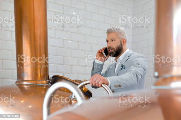 Businessman Using Mobile Phone In His Micro Brewery Stock Photo - Download Image Now