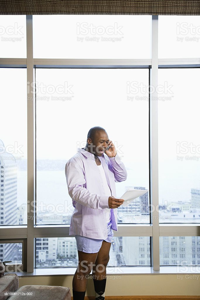 Businessman using mobile phone in hotel room, shouting Lizenzfreies stock-foto