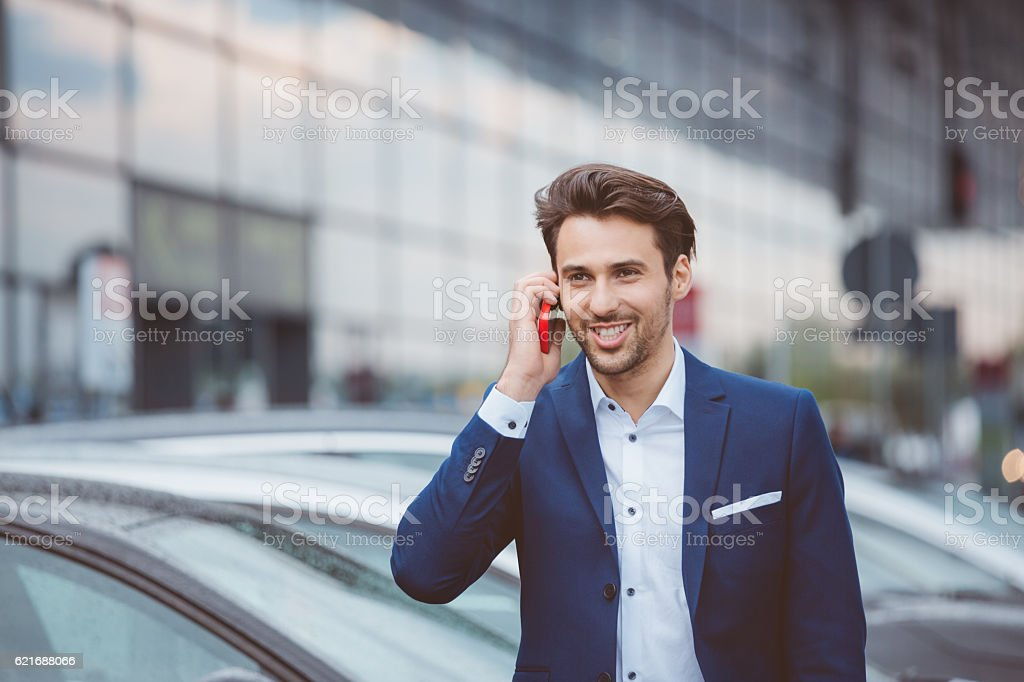 Businessman using mobile phone in parking lot stock photo